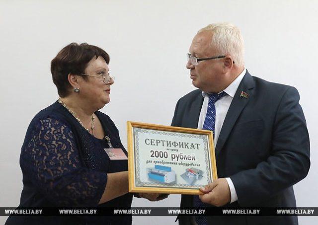 Председатель Витебского областного Совета депутатов Владимир Терентьев вручает сертификат директору центра социального обслуживания Наталье Ивановой