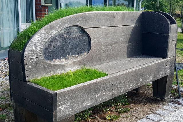 Скамейка натерритории деревни. Травку посадили специально, чтобы люди могли еетрогать